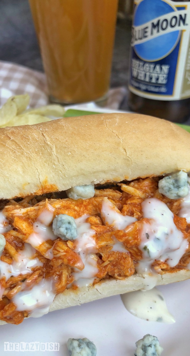 Easy 4 Ingredient Crockpot Shredded Buffalo Chicken Sandwiches -- Looking for easy slow cooker chicken recipes? This one is a keeper and made with simple ingredients! It's great for lunch, dinner and parties-- game day! The Lazy Dish #thelazydish #crockpot #buffalochicken #slowcooker